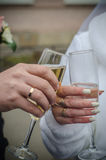 Glasses of wine in the hands of the bride and groom Stock Photography