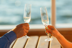 Happy couple drinks champagne on a yacht. Glasses of wine in the hands of woman Stock Images