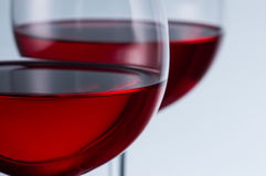 Glasses of wine on a light background. Two glasses of wine on a light background Royalty Free Stock Image