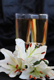 Glasses with wine and lily flower. On black silk Royalty Free Stock Images
