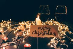 Glasses with wine and merry christmas card. Two glasses with red wine on wooden table with fairylights, candles and merry christmas card Royalty Free Stock Photo
