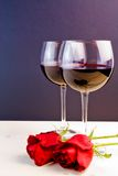 Glasses of wine near red roses Stock Photography