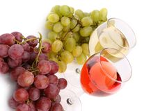 Glasses of wine and ripe grapes isolated on white Royalty Free Stock Images