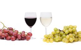 Glasses of wine and ripe grapes isolated on white Stock Photos