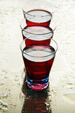 Glasses of wine on a wet mirror. Stock Photos