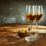 Glasses of Wine on Wooden Table with Green Olives stock image