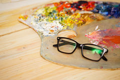 Glasses, wooden palette and oil paints Royalty Free Stock Photo