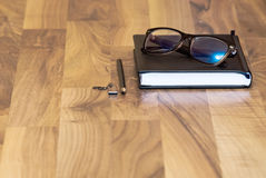 Glasses on a wooden table. With a pen and a flash card Stock Photography