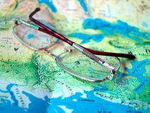 Glasses world Map. Close up glasses on world Map stock photos