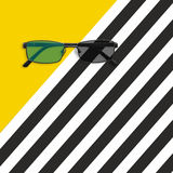 Glasses on the yellow and black white striped background. Flat lay Royalty Free Stock Images