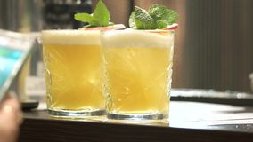 Glasses of yellow cocktails. Taking drink from the bar counter stock video footage