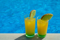 Glasses with yellow and green cocktail in front of a swimming pool with clear water. Close-up photo. Top view at glasses with Royalty Free Stock Image