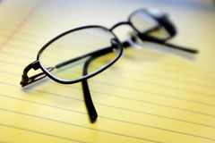 Glasses on Yellow Notepad in Office. Glassed on yellow notepad in office Stock Photo