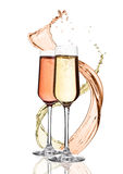 Glasses of yellow and pink champagne with splashes royalty free stock photography