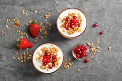 Glasses with yogurt, berries and granola on table. Top view Stock Photos