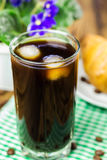 Glassful of black coffee with ice on green napkin. croissant, flowerpot, wooden table, selective focus Stock Image