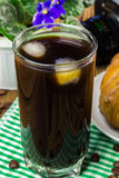 Glassful of black coffee with ice on green napkin. croissant, vintage camera, flowerpot, wooden table, selective focus.  stock image
