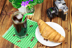 Glassful of black coffee with ice and tubule on green napkin. croissant, vintage camera, flowerpot, wooden table.  Royalty Free Stock Photos