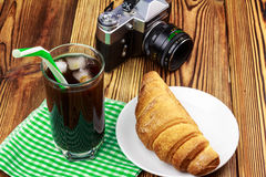 Glassful of black coffee with ice and tubule on green napkin. croissant, vintage camera, wooden table in cafe. Travel concept Stock Photo