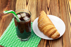 Glassful of black coffee with ice and tubule on green napkin. croissant, wooden table in cafe. Glassful of black coffee with ice and tubule on green napkin Royalty Free Stock Photo