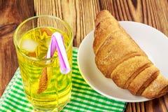 Glassful cytryny soda z lodem i tubule na zielonej pielusze croissant, drewniany stół zdjęcie royalty free