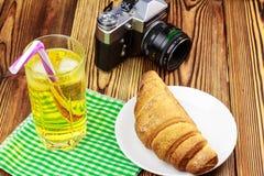 Glassful cytryny soda z lodem i tubule na zielonej pielusze croissant, rocznik kamera, drewniany stół zdjęcie stock