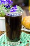 Glassful czarna kawa na zielonej pielusze croissant, flowerpot, drewniany stół, selekcyjna ostrość obrazy stock