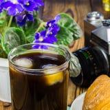Glassful czarna kawa z lodem, croissant, rocznik kamera, flowerpot na drewnianym stole, selekcyjna ostrość zdjęcie stock