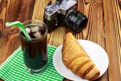 Glassful czarna kawa z lodem i tubule na zielonej pielusze croissant, rocznik kamera, drewniany stół w kawiarni zdjęcie stock