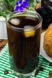 Glassful czarna kawa z lodem na zielonej pielusze croissant, rocznik kamera, flowerpot, drewniany stół, selekcyjna ostrość obraz stock