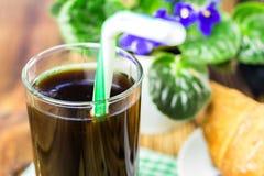 Glassful czarna kawa z tubule, croissant, flowerpot na drewnianym stole, selekcyjna ostrość zdjęcie stock