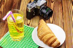 Glassful of lemon soda with ice and tubule on green napkin. croissant, vintage camera, wooden table. Glassful of lemon soda water with ice and tubule on green Stock Photo