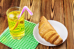 Glassful of lemon soda with ice and tubule on green napkin. croissant, wooden table. Glassful of lemon soda water with ice and tubule on green napkin. croissant Royalty Free Stock Images