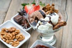 Glassglasscoupe med garnering, choklad, valnötter och skivad jordgubbe Royaltyfri Foto