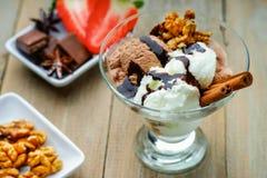 Glassglasscoupe med garnering, choklad, valnötter och skivad jordgubbe Royaltyfria Foton
