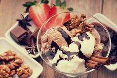 Glassglasscoupe med garnering, choklad, valnötter och skivad jordgubbe Royaltyfri Bild