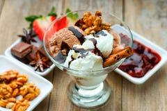 Glassglasscoupe med garnering, choklad, valnötter, skivad jordgubbe och driftstopp Arkivbilder