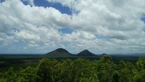 Glasshouse Mountains of Australia. View of the Glass House Mountains in Queensland, Australia on a summer day with white clouds Stock Photography