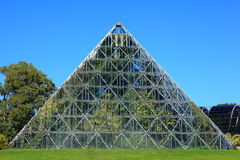 Glasshouse pyramid in park. The tropical plant house pyramid at the Sydney Royal Botanic Gardens - soon to be knocked down and replaced - set against clear blue Stock Images