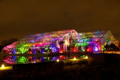 The glasshouse at Wisley, Surrey, glowing with bright coloured lights, reflected in the water. Stock Image
