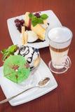 Glasskopp-, cake- och kaffelatte på tabellen Royaltyfri Foto