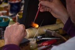 Glassmakeren formar exponeringsglas in i folkdiagram Arkivbilder