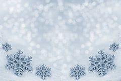 Glasspielzeugschneeflocke auf Schneehintergrund Stockbilder