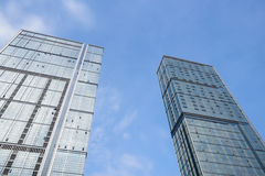 Glasswalled buildings towering in sunny sky Royalty Free Stock Image
