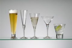 Glassware. Assorted cocktail glasses, one with beer, one with white wine and one with clear alcohol Royalty Free Stock Photo