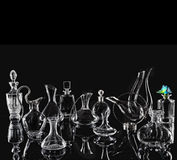 Glassware on the black background. Glass carafes and various glassware with metal on the black background Royalty Free Stock Photos