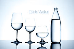 Glassware and bottle filled with water on white background.  stock image
