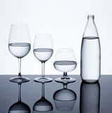 Glassware and bottle filled with water on white background.  royalty free stock photos