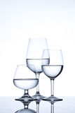 Glassware and bottle filled with water on white background.  royalty free stock images