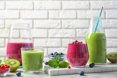 Glassware of fresh yogurt smoothie with berries and kiwi. On light table stock photo